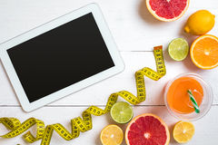 Fitness concept with fruit, a glass of juice and centimeter. Top view background concept. Fitness concept with fruit, bowl of oatmeal and centimeter. Top view Stock Image