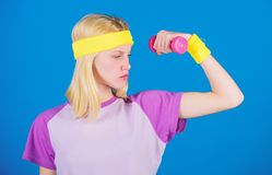 Fitness concept. Girl exercising with dumbbell. Fitness instructor hold little dumbbell blue background. How to get. Toned physique. Beginner dumbbell exercises stock photo