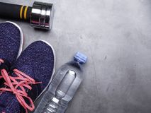 Fitness concept background with sneakers with Coral shoelaces Color of the year 2019. Main trend concept , dumbbells, water bottle. Fitness concept on grey royalty free stock images