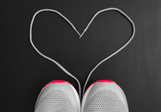 Fitness concept. Love to sport. Sneakers sport shoes with shoelaces as form of heart on black background.  royalty free stock photo