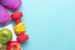 Fitness concept with mix fruits, dumbbells, measuring tape and sport shoes on bright cyan background. Stock Photo