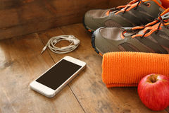 Fitness concept with mobile phone with earphones, towel, apple and sport footwear over wooden background. Royalty Free Stock Photography