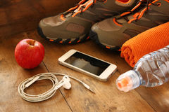 Fitness concept with mobile phone with earphones, towel, apple and sport footwear over wooden background. Stock Image