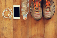 Fitness concept with mobile phone with earphones, towel and sport footwear over wooden background Royalty Free Stock Photos