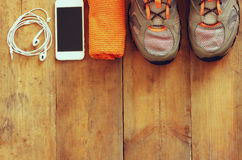 Fitness concept with mobile phone with earphones, towel and sport footwear over wooden background.  Royalty Free Stock Photography
