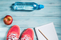 Fitness concept, pink sneakers, red apple, bottle of water and notebook with pencil on wooden background, top view Stock Photography