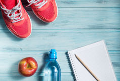 Fitness concept, pink sneakers, red apple, bottle of water and notebook with pencil on wooden background, top view Royalty Free Stock Photography