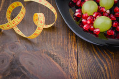 Fitness concept with pomegranate, grapes in black plate and centimeter. Fitness background with pomegranate, grapes in black plate and centimeter Stock Photos