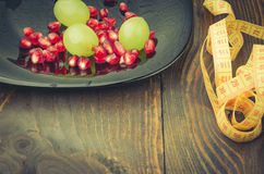 Fitness concept with  pomegranate, grapes, centimeter. Fitness background with pomegranate, grapes, centimeter Stock Photography
