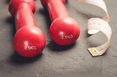 Fitness concept with red dumbbells and measuring tape/ fitness concept with red dumbbells and measuring tape on a dark background. Fitness concept with red royalty free stock photo