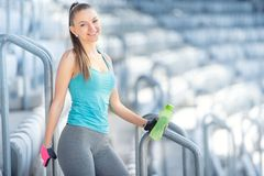 Fitness concept - sexy woman drinking water during workout and training. Cross fit workout on stairs, squats Stock Images