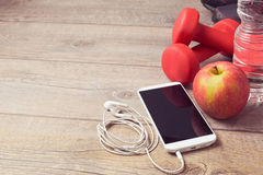 Fitness concept with smartphone and apple on wooden background Royalty Free Stock Photography