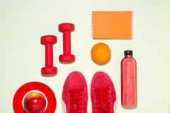 Fitness concept. Sneakers, apple, dumbbell and fruit juice bottl. E on pastel color background Stock Photo
