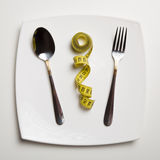 Fitness concept. Spoon and fork on white plate. Measuring tape b Stock Images