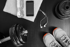 Fitness concept. Sport equipment. Sneakers & x28;sport shoes& x29;, towel, bottle of water, earphones, dumbbells and phone on black background Stock Photo