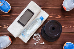 Fitness concept. Sport equipment. Sneakers & x28;sport shoes& x29;, towel, bottle of water, earphones, dumbbells and phone on wooden background Stock Image