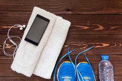 Fitness concept. Sport equipment. Sneakers & x28;sport shoes& x29;, towel, bottle of water, earphones & x28;headphones& x29; and phone on wooden background Royalty Free Stock Photos