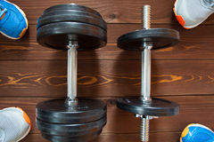 Fitness concept. Sport equipment. Sneakers sport shoes and  dumbbells on wooden background Royalty Free Stock Images
