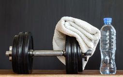 Fitness concept.  Sport equipment.Towel, bottle of water and dumbbells on black  background. Stock Photo