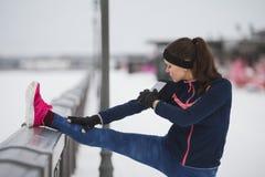 Fitness concept - sport girl model runner doing flexibility exercise for legs before run at snow winter promenade Stock Photo