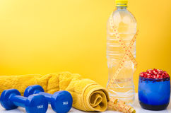 Fitness concept with towel, bottle, centimeter and dumbbells Stock Images