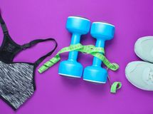 Fitness concept. Weight loss. Sports bra,shoes, dumbbells, ruller on purple background. Top view, flat lay royalty free stock photography