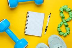 Fitness concept. Workout plan. Plastic blue dumbbells, sport shoes, notepad, ruler on a yellow background. The idea of ​​losing weight. Top view royalty free stock image