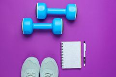 Fitness concept. Workout plan. Sport shoes, plastic blue dumbbells, notepad on purple background. Top view. Flat lay royalty free stock photo