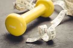 Fitness concept with yellow dumbbell and measuring tape/fitness concept with yellow dumbbell and measuring tape on a dark. Background stock photo