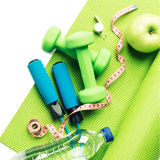 Fitness concept - yoga mat, apple, dumbbells and skipping rope Stock Photo