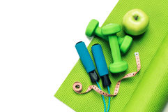 Fitness concept - yoga mat, apple, dumbbells and skipping rope Royalty Free Stock Photos