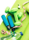 Fitness concept - yoga mat, apple, dumbbells and skipping rope Stock Photos