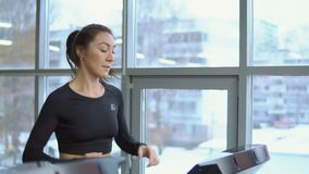 Fitness concept. Young beautiful woman on a treadmill in the gym. Slow motion stock video footage