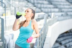 Fitness concept - young woman drinking water during workout, training. Cross fit workout on stairs, squats and exercises. Fitness concept - young woman drinking Royalty Free Stock Photography