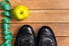 Fitness concepten - sportkleren met vruchten en het meten van band, houten achtergrond Stock Foto