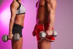 Fitness couple. Male and female in fitness attire holding dumbbell on Purple background Royalty Free Stock Photo