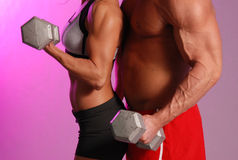 Fitness couple. Male and female in fitness attire holding dumbbell on Purple background Royalty Free Stock Photos