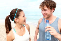Fitness couple on beach. Talking relaxing and smiling happy after running training. Multiracial couple: Asian women and Caucasian men drinking water royalty free stock photography