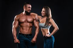 Fitness couple on a black background looking each other and smiling royalty free stock photo