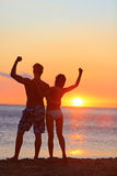 Fitness couple cheering at beach sunset. Happy romantic fit young couple enjoying sunset with arms raised up flexing muscles together. People on sports Royalty Free Stock Photography