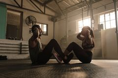 Fitness couple doing abs workout in gym royalty free stock photo