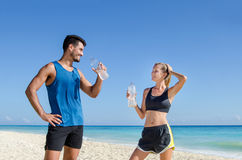 Fitness. Couple drink water after training at the beach Stock Image