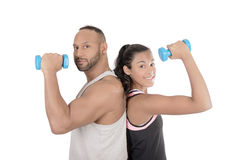 Fitness couple with dumbbells. Horizontal composition of a fitness couple lifting dumbbells. Isolated royalty free stock images