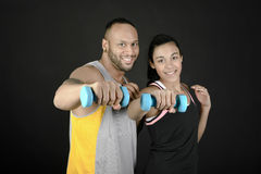 Fitness couple with dumbbells. Horizontal composition of a fitness couple looking at camera and lifting dumbbells royalty free stock photo