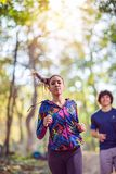 Fitness couple enjoying in a healthy lifestyle while jogging along a forest, exercise and fitness concept. Young fitness couple enjoying in a healthy lifestyle royalty free stock image
