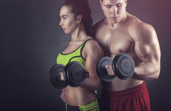 Fitness couple. Exercise with dumbbells on a black background stock photo