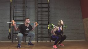Fitness couple exercising in gym with barbell weights. Slow motion stock footage