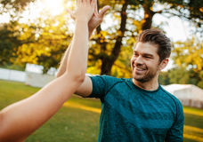 Fitness couple giving high five in park. Stock Photos