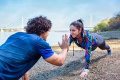 Fitness couple giving high five to each other while doing push u royalty free stock image