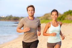 Fitness couple jogging outside on beach smiling. In summer sunset. Young mixed race asian female model running on beach with handsome caucasian male royalty free stock photo